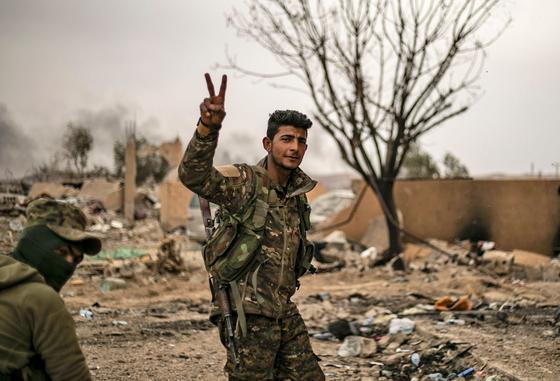 24일 IS 최후거점인 시리아 동부 바구즈를 탈환한 시리아민주군이 승리의 V자를 표시하고 있다.[AFP=연합뉴스]