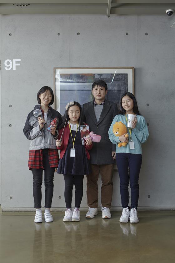 (왼쪽부터)김나연·이은채 학생기자, 유성운 작가, 진효원 학생모델이 포즈를 취해 보였다. 학생기자단은 각자 준비한 굿즈를 들었다. 이은채 학생기자는 BTS 멤버 정국의 포토카드를 꼭 찍어야 한다고 인터뷰 내내 들고 다녔다.