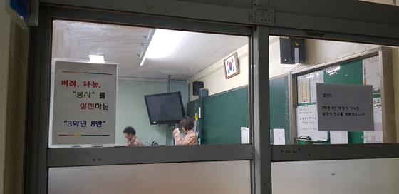 지난 23일 오후 충남 홍성여중 부설 방통중학교 신입생들이 자기 소개를 하고 있다. 1학년 2반 담임 김희정 교사(오른쪽)가 사연을 듣다 눈물을 닦고 있다. 신진호 기자
