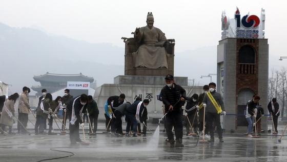초미세먼지 주의보가 발령된 지난 20일 오전 서울 광화문광장에서 서울시·종로구 관계자와 주민들이 물청소를 하고 있다. 서울시는 오는 31일까지 서울 전역에서 '새봄맞이 대청소'를 실시, 시내 모든 도로에서 대대적인 미세먼지 제거에 나선다고 밝혔다. [뉴스1]
