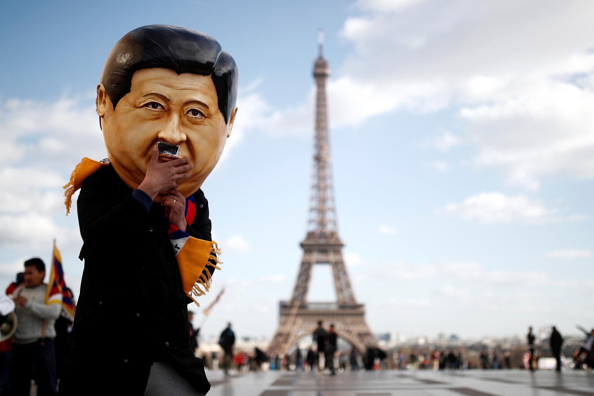 콧수염을 붙인 시진핑 중국 국가주석의 탈을 쓴 한 사람이 25일(현지시간) 프랑스 파리 에펠탑 앞에 서 있다. [로이터=연합뉴스]