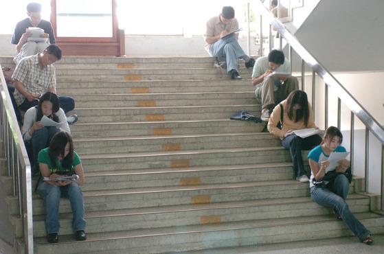 국가기술자격시험'에 지원한 응시자들이 시험 시작 전 계단에 앉아 수험서를 보며 마지막 정리를 하고 있다. [중앙포토]