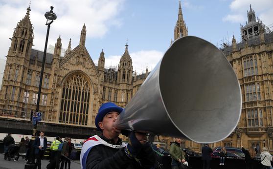 브렉시트 반대 시위대가 메가폰을 잡고 의회를 향해 말을 들어달라고 하고 있다. [AP=연합뉴스]