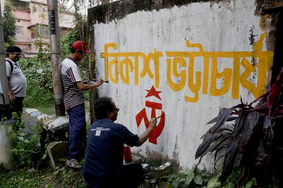 인도공산당에서 분리한 정당인 '인도공산당 마르크스주의자(CPI-M)'의 당원들이 16일 동부 대도시 콜카타의 벽에 출마 후보의 이름을 쓰고 당의 상징을 그려넣고 있다. 인도에선 극좌에서 극우까지 다양한 정당이 공존한다 [AP=연합뉴스]
