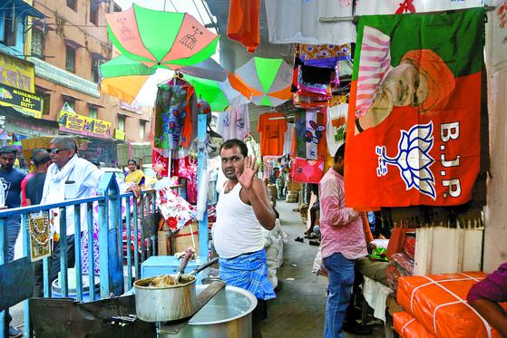 3월 15일 인도 동부 대도시 콜카타의 시장에 집권당인 BJP의 당명과 상징인 연꽃, 그리고 당 대표인 나렌드라 모디 총리의 모습이 인쇄된 깃발이 걸려 있다. BJP는 힌두민족주의를 내세운 정당으로 경제성장 정책으로 인기를 모아왔다. [AP=연합뉴스]
