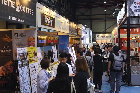 많은 직장인이 퇴직금으로 요식업 창업을 꿈꾼다. 하지만 식당은 아무나 하는 만만한 사업이 아니다. 사진은 서울의 한 프랜차이즈 창업박람회를 찾은 사람들의 모습. [연합뉴스]