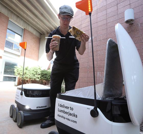 지난 26 일 애리조나 대학교 북부 캠퍼스 식당 직원 Michael Sherman가 애리조나주 플래그 스태프 (Flagstaff)에서 배달 로봇에 음식을 담고 있다. [AP=연합뉴스]