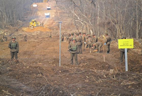 지난해 11월 22일 중부전선 군사분계선 너머로 북한군이 도로연결작업을 하고 있다.[국방부 제공]
