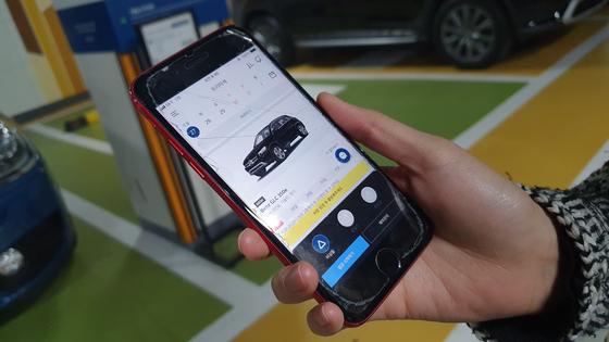 지난 27일 서울 성수동 트리마제 아파트 지하 주차장에서 신혜수(27)씨가 스마트폰으로 공유할 수입차를 고르는 모습. 윤상언 기자