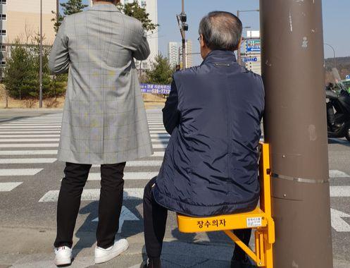 지난달 29일 경기 남양주시 별내동 별사랑마을 횡단보도 앞에 시범 설치된 장수의자. 한 노인이 앉아서 신호를 기다리고 있다. 남양주경찰서는 1일 오후 1시 별내동에 총 60개의 의자를 설치한다.[사진 별내파출소]