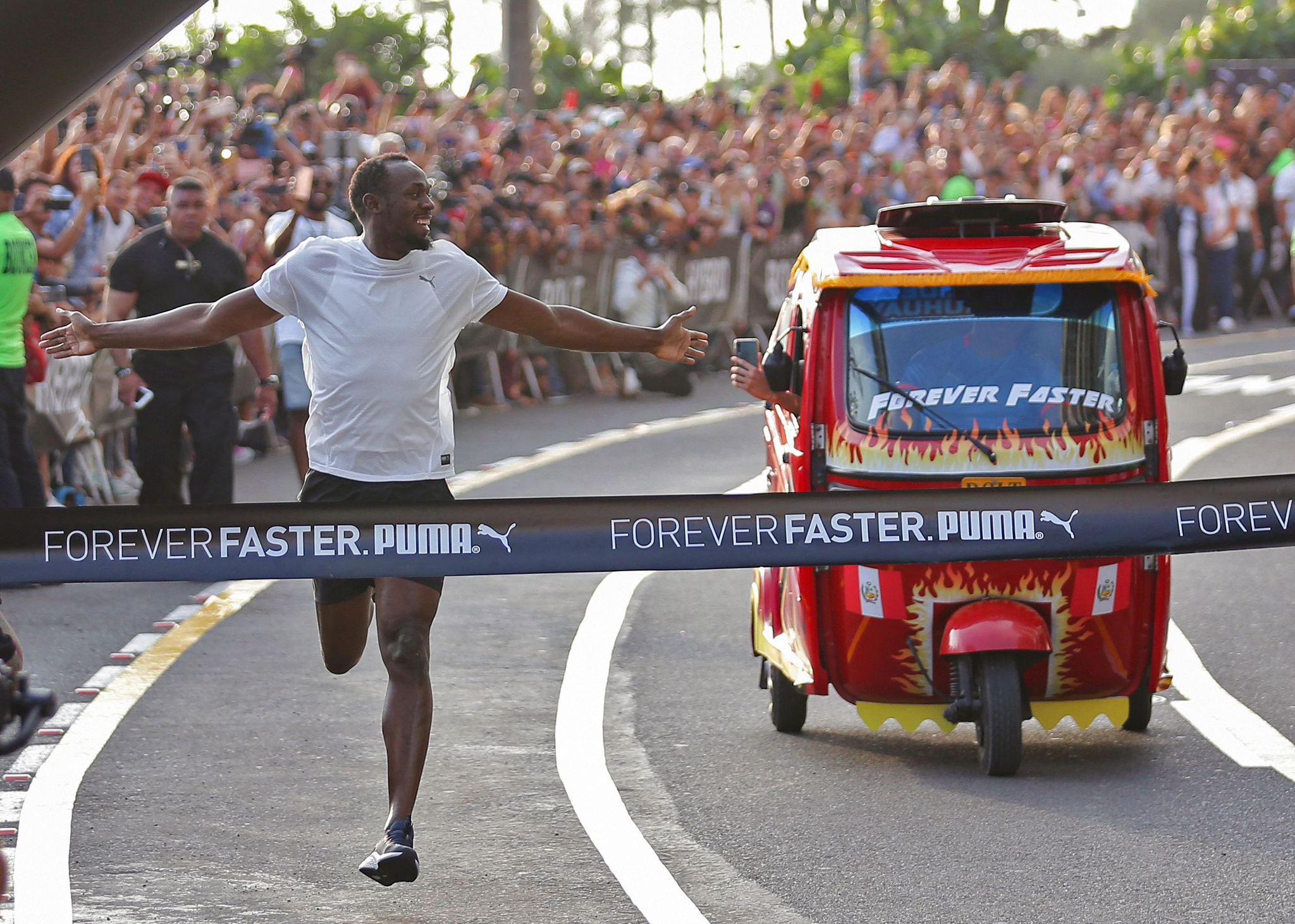 우사인 볼트가 2일(현지시간) 페루 리마에서 열린 '모토 택시'와의 50m 경주에서 결승선을 통과하고 있다.[AFP=연합뉴스]