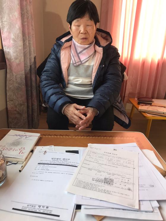 제주 4.3 당시 허리 부상을 입어 후유장애인 신청을 했지만 국가로부터 '불인정' 결과를 받은 강양자씨가 소송 관련 서류를 보이고 있다. 최충일 기자
