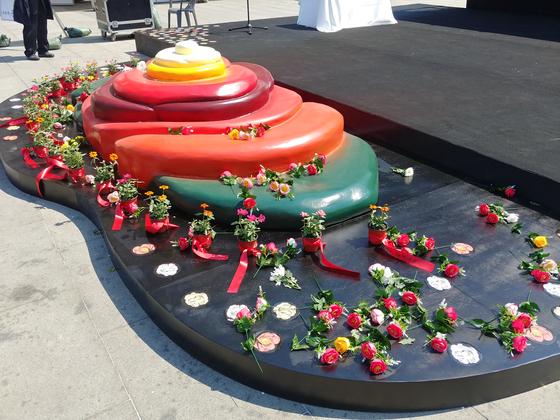 제주 4.3 광화문 추념식 무대 앞 설치된 동백꽃 조형물과 헌화된 꽃들. 김정연 기자