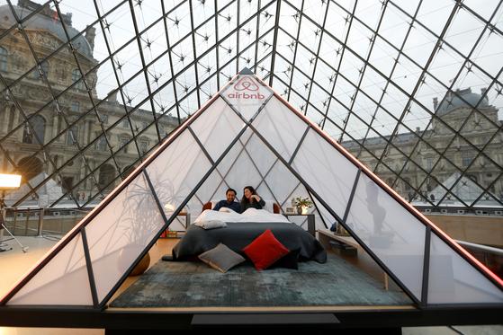 에어비앤비 직원들이 지난달 12일(현지시간) 프랑스 파리 루브르 박물관 유리 피라미드안에서 숙박 이벤트 리허설을 하고 있다. [로이터=연합뉴스]