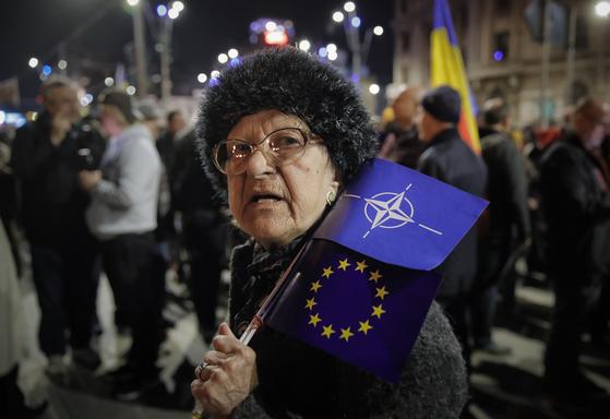 3월 30일 루마니아 수도 부카레스트에서 정부의 사법권 남용을 규탄하는 시위에 참가한 시민이 나토와 유럽연합(EU) 깃발을 들고 있다. 루마니아는 냉전 시절 공산권에 속했지만 국민이 차우세스쿠 정권을 전복하고 민주 국가로 재출발하면서 나토와 EU 회원국이 됐다. 이 나라에서 나토와 EU는 민주주의와 인권, 시장경제라는 가치를 상징함을 보여주는 장면이다. [AP=연합뉴스]