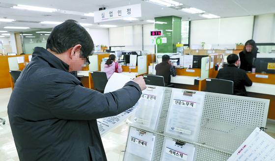 지난달 20일 유모(57)씨가 서울 중구 서울고용복지센터에서 구직 자료를 살펴보고 있다. 유씨를 비롯해 추락한 5060 중산층 중 상당수는 취직하지 못한 자녀를 부양하면서 자식들의 학자금 대출까지 대신 갚아주고 있었다. [우상조 기자]