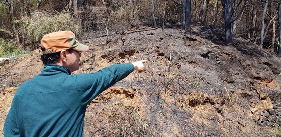 지난 2일 발생한 부산 해운대구 운봉산 산불 현장과 불과 15m 떨어진 곳에 살고 있는 조도제(65)씨가 발화 지점으로 추정되는 곳을 가르키고 있다. 이은지 기자