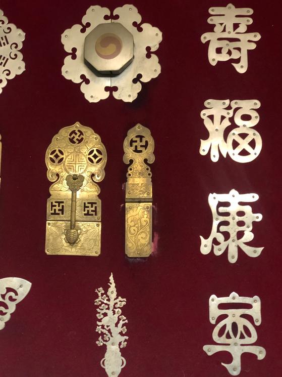 수복강녕 장석. 가구의 장석은 자연물의 문양과 문자 모양, 기하학적 문양 등으로 사람들의 염원을 표현하고 있다. 수(壽)자와 복(福)자 문양은 오래 살고 복을 누리기를 바라는 소망을 상징한다. [사진 이정은]