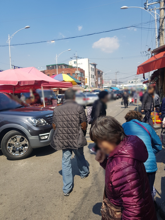 지난 3일 오전 서울 동대문구 청량리 청과물 도매시장에서 한 80대 노인 뒤로 SUV 차량이 바짝 다가섰다. 노인은 차량이 울리는 경적을 알아채지 못하고 천천히 길을 걸어갔다. 임선영 기자