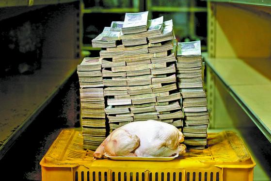 베네수엘라의 초인플레이션을 보여주는 상징적인 사진. 지난해 8월 카라카스의 한 상점에서 2.4㎏짜리 생닭 한 마리가 1460만 볼리바르(약 2500원)에 거래됐다. 베네수엘라는 화폐개혁을 통해 새 통화 '볼리바르 소베라노(최고 볼리바르)'를 도입하는 등 물가를 잡으려 애쓰고 있지만 올해 물가상승률은 세계 현대사에서 유례 없는 규모인 1000만%에 이를 것으로 예상된다. [로이터=연합뉴스]