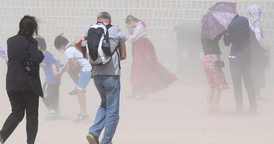 5일 전국에서 황사가 발생, 미세먼지 농도가 높아질 것으로 국립환경과학원이 예보했다. 사진은 2017년 5월 6일 서울 경복궁을 찾은 관광객들이 황사 먼지를 피해 몸을 돌리고 있다. [중앙포토]