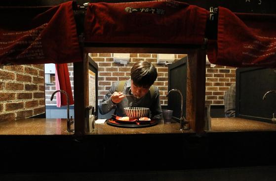 서울 신촌의 일본식라면 전문점 이찌멘의 1인전용 식사공간에서 한 시민이 식사를 하고 있다. 통계청이 지난해 9월 발표한 '인구주택총조사에 나타난 1인 가구 현황 및 특성'에 따르면 2017년 1인 가구는 562만가구로 2000년 222만가구보다 340만가구(152.6%) 증가했다. 일반가구 대비 1인 가구 비율도 2000년 15.5%에서 2017년 28.6%로 크게 상승했다. 1인가구가 증가하며 이른바 '혼밥', '혼술'도 이제는 일반적인 문화가 됐다. [뉴스1]