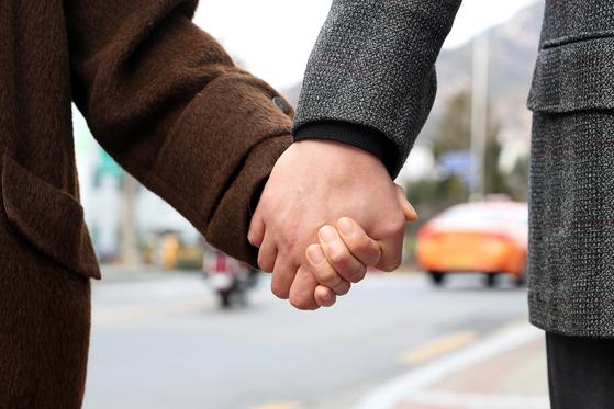 지난달 14일 서울 은평구 여성인력개발센터에 들러 교재를 살펴보고 있는 김현지(가명)씨(아래 사진). 이날 김씨와 남편은 두 손을 꼭 잡고 걸었다. 두 사람은 재기의 꿈을 꾸고 있다. [장진영 기자]