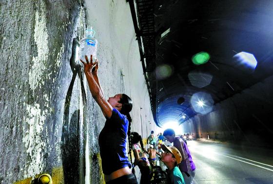 식수를 구하려는 베네수엘라 시민들이 1일(현지시간) 수도 카라카스의 한 터널에서 흘러나오는 물을 받고 있다. 지난달 말부터 대규모 정전이 계속되면서 카라카스 시내의 고지대와 식수를 저장한 물탱크 주변에 긴 줄이 형성됐다. [AP=연합뉴스]