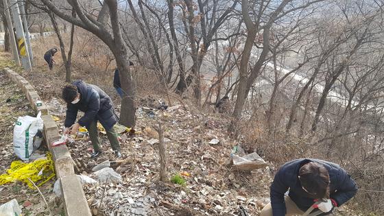 충남 예산경찰서 형사들이 백골시신이 발견된 예산군 신양면 차동고개 중턱 비탈길에서 현장조사를 하고 있다. [사진 예산경찰서]