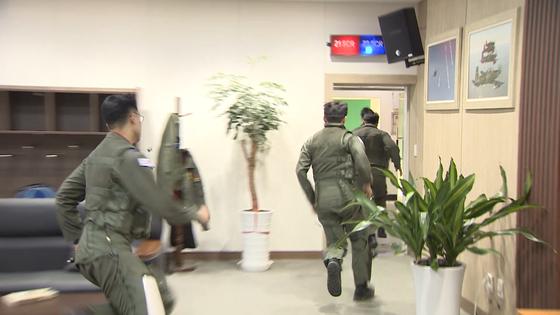 비상 출격 명령을 받은 전투기 조종사가 격납고를 향해 뛰쳐 나가고 있다. [JTBC 영상캡처=박승영]