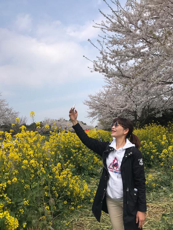지난 5일 10㎞의 벚꽃과 유채꽃길이 펼쳐진 제주도 서귀포시 표선면 가시리 녹산로에서 한 관광객이 사진을 찍고 있다. 최충일 기자