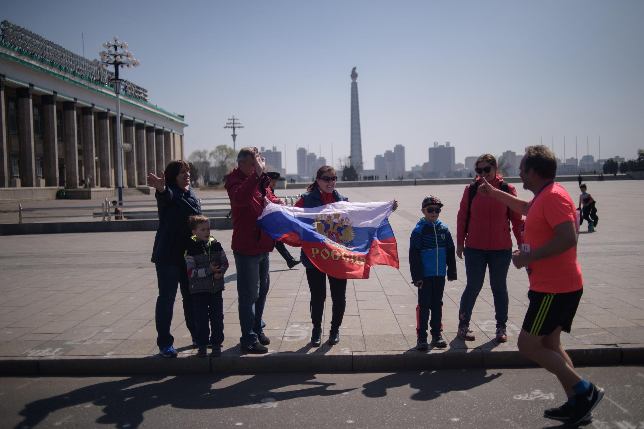 러시아 국기를 든 관광객들이 달리는 선수를 응원하고 있다. [AFP=연합뉴스]