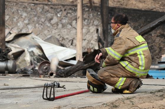 사진은 지난 6일 강원 속초시 장사동에서 잔불을 제거하다 휴식을 취하는 소방관 모습.[연합뉴스]