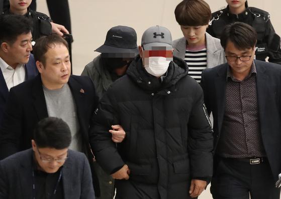 거액의 '빚투' 논란을 촉발한 래퍼 마이크로닷의 부모 신모씨 부부(가운데 눈 주위 모자이크)가 8일 오후 인천국제공항을 통해 귀국한 뒤 경찰에 체포돼 공항을 빠져나가고 있다. [연합뉴스]