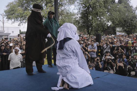 지난해 4월20일 인도네시아 반다 아체의 이슬람사원(모스크)에서 샤리아법 집행관이 얼굴을 가린 채 꿇어 앉는 여성 무슬림에게 채찍 태형을 가하고 있다. 이 여성은 성매매 혐의로 구속 수감돼 왔다. 이날 또다른 남녀 커플은 공공장소에서 애정 행각을 했다는 이유로 마찬가지로 공개 태형을 당했다. [AP=연합뉴스]