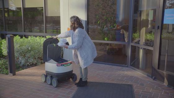 스타십 로봇이 무인배송한 물건을 소비자가 스마트폰을 이용해 꺼내고 있다. [사진=스타십 테크놀로지]