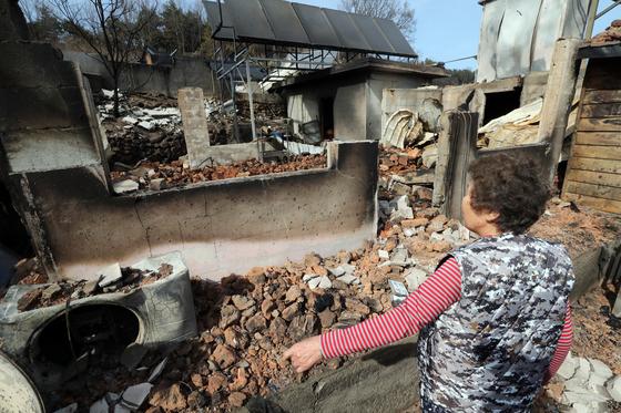 산불 발생 나흘째인 7일 큰 피해를 입은 강원 속초시 장사동 장천마을의 한 주민이 폐허가 된 집을 바라보고 있다. [연합뉴스]