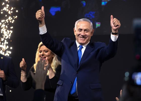 9일(현지시간) 치러진 이스라엘 총선 결과를 기다리면서 리쿠드당 대표인 베냐민 네타냐후 총리(오른쪽)가 아내 사라 여사와 함께 지지자들의 환호에 답하고 있다. 네타냐후 총리는 이번 선거 결과로 이스라엘 최장수 총리(5선) 자리를 예약한 상태다. [EPA=연합뉴스]
