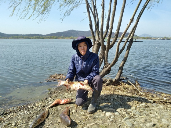 지난 7일 경기도 고양시 행주대교 인근 한강하구에서 잡힌 등 굽은 물고기를 어민이 들어보이고 있다. [사진 행주어촌계]