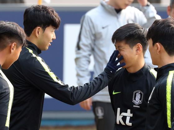 축구대표팀 주장 손흥민(왼쪽 두 번째)이 A팀 훈련에 처음 참가한 이강인(왼쪽 세 번째)의 긴장을 풀어주기 위해 얼굴을 손으로 문지르며 장난을 치고 있다. [연합뉴스]