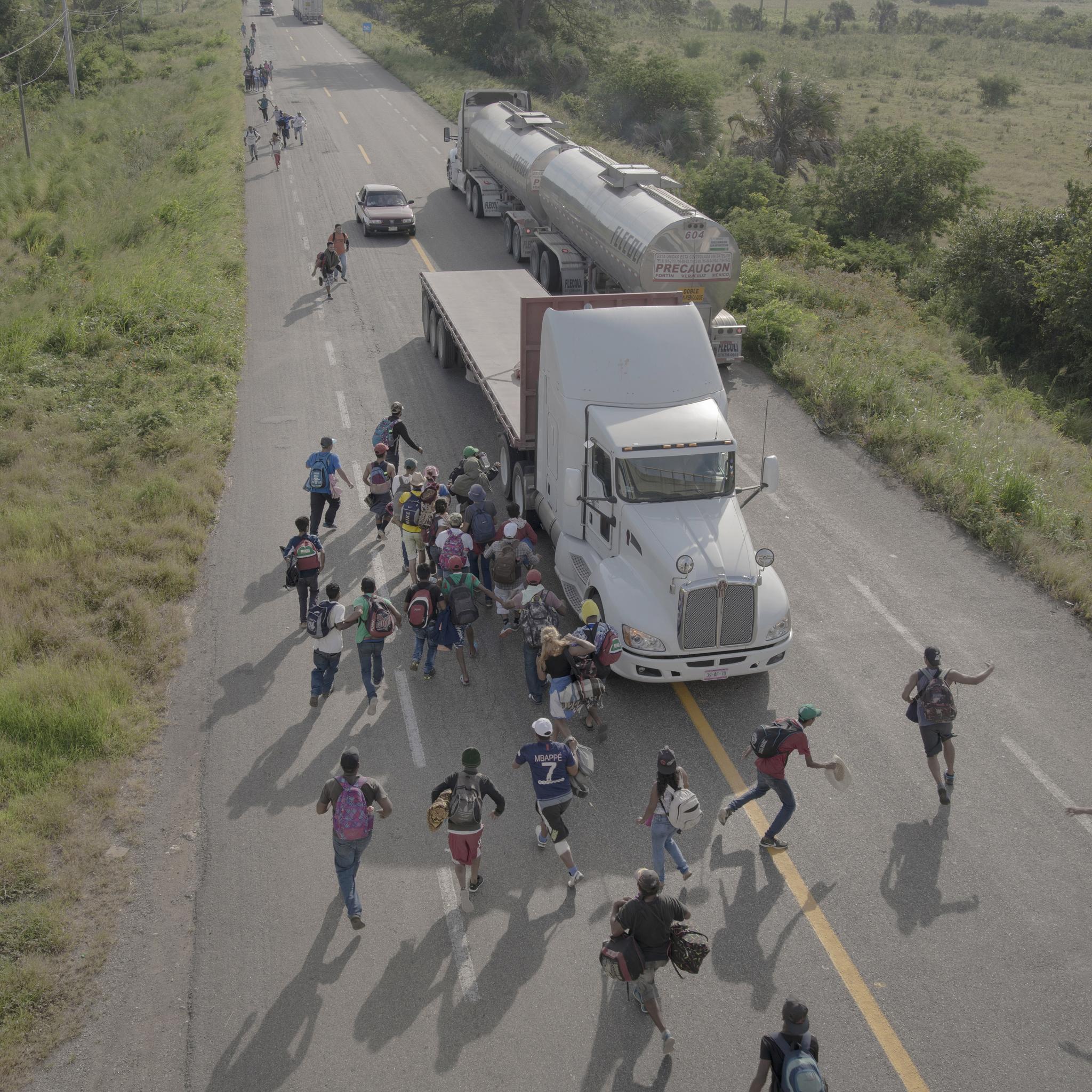 작년 10월 멕시코의 한 도시에서 난민들이 미국 국경방향으로 가는 한 트럭에 올라타고 있다. 대부분의 트럭 운전기사들은 난민들을 가는 방향까지 무료로 태워주고 있다.[EPA=연합뉴스]