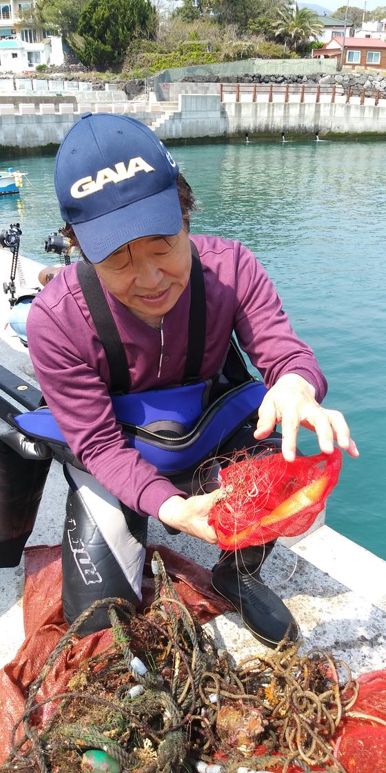 전재경 자연환경국민신탁 대표가 지난 7월 제주도 서귀포 남서쪽 범섬 인근 바다 밑에서 건져올린 낚시줄과 주낙 등을 살펴보고 있다. [사진 자연환경국민신탁]