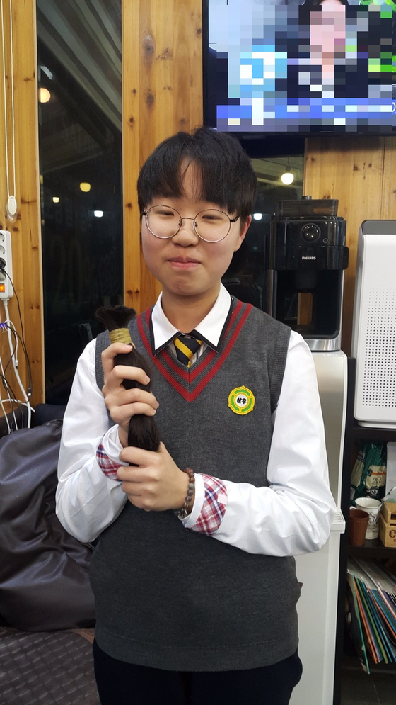 지난해에 이어 올해도 백혈병 등 소아암 환자를 위해 모발을 기증한 삼우중 2학년 김예윤(14)양이 지난 8일 미용실에서 본인 머리를 들고 수줍게 웃고 있다. 머리가 덜 자라 바투 깎아 상고머리가 됐다. [사진 학부모]