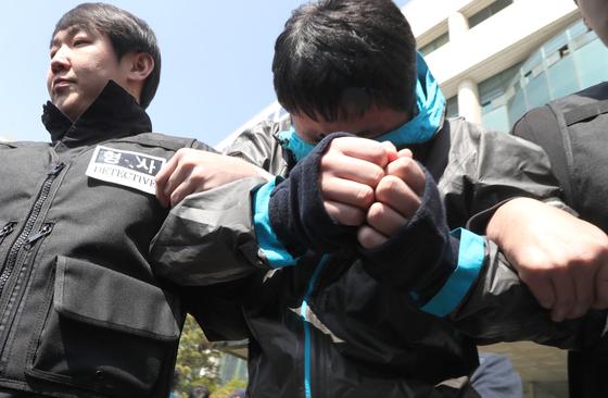 이희진 부모를 살해한 피의자 김다운이 지난달 26일 오후 안양동경찰서에서 검찰 조사를 받기 위해 호송차로 이동하고 있다. 최승식 기자