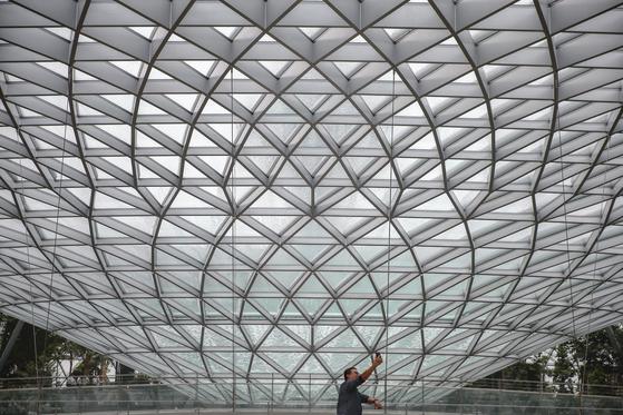 """주얼 창이를 설계한 건축가 모세 사프디는 """"영화 아바타에서 공항 디자인의 영감을 받았다""""고 말했다. 지난 11일 주얼 창이를 방문한 한 남성이 사진을 찍고 있다.[EPA=연합뉴스]"""