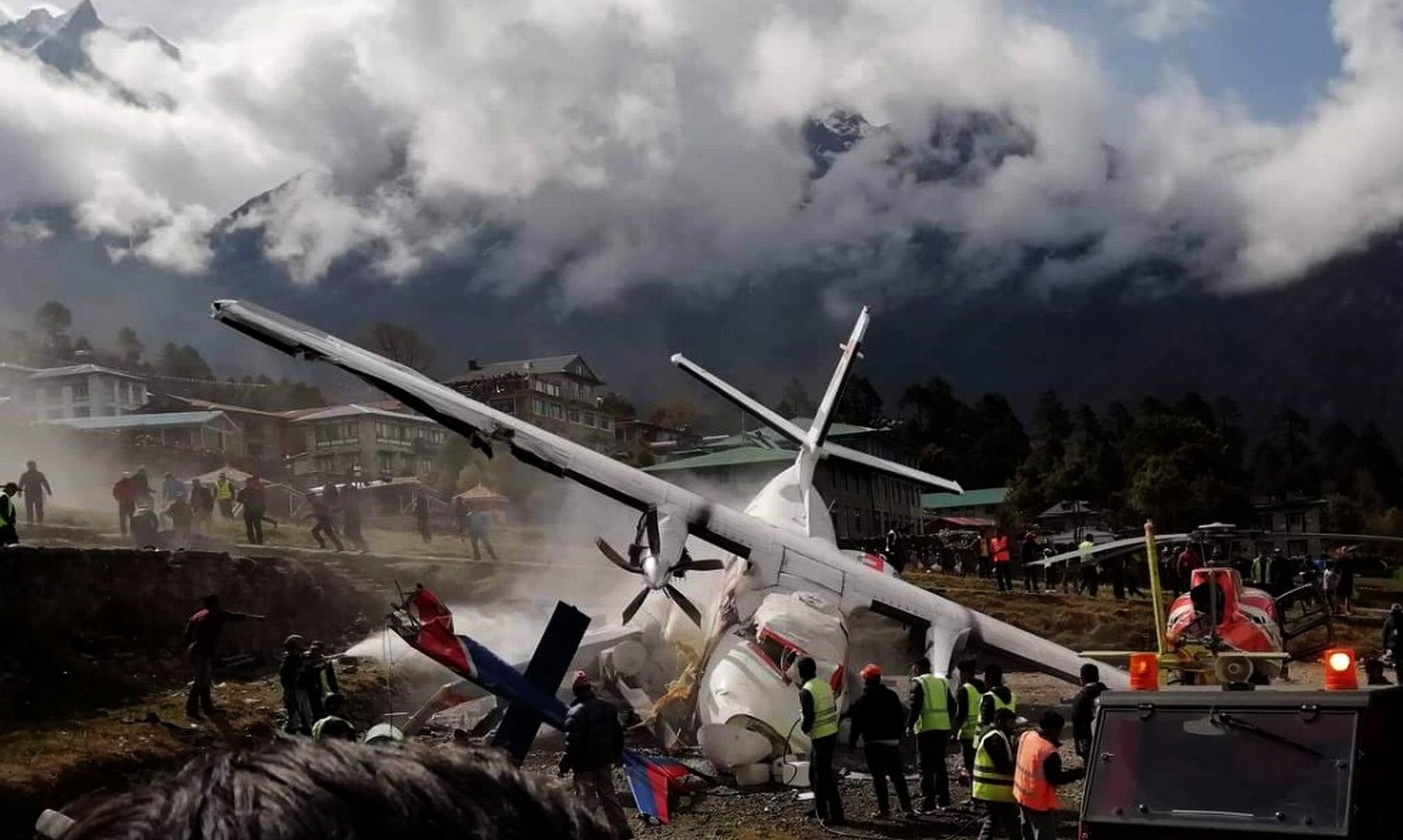 14일(현지시간) 네팔 에베레스트산 관문 루클라의 텐징 힐러리 공항에서 충돌한 서미트항공 소속 소형비행기와 헬리콥터의 부서진 기체 사이에서 하얀 연기가 뿜어져 나오고 있다.[신화=연합뉴스]