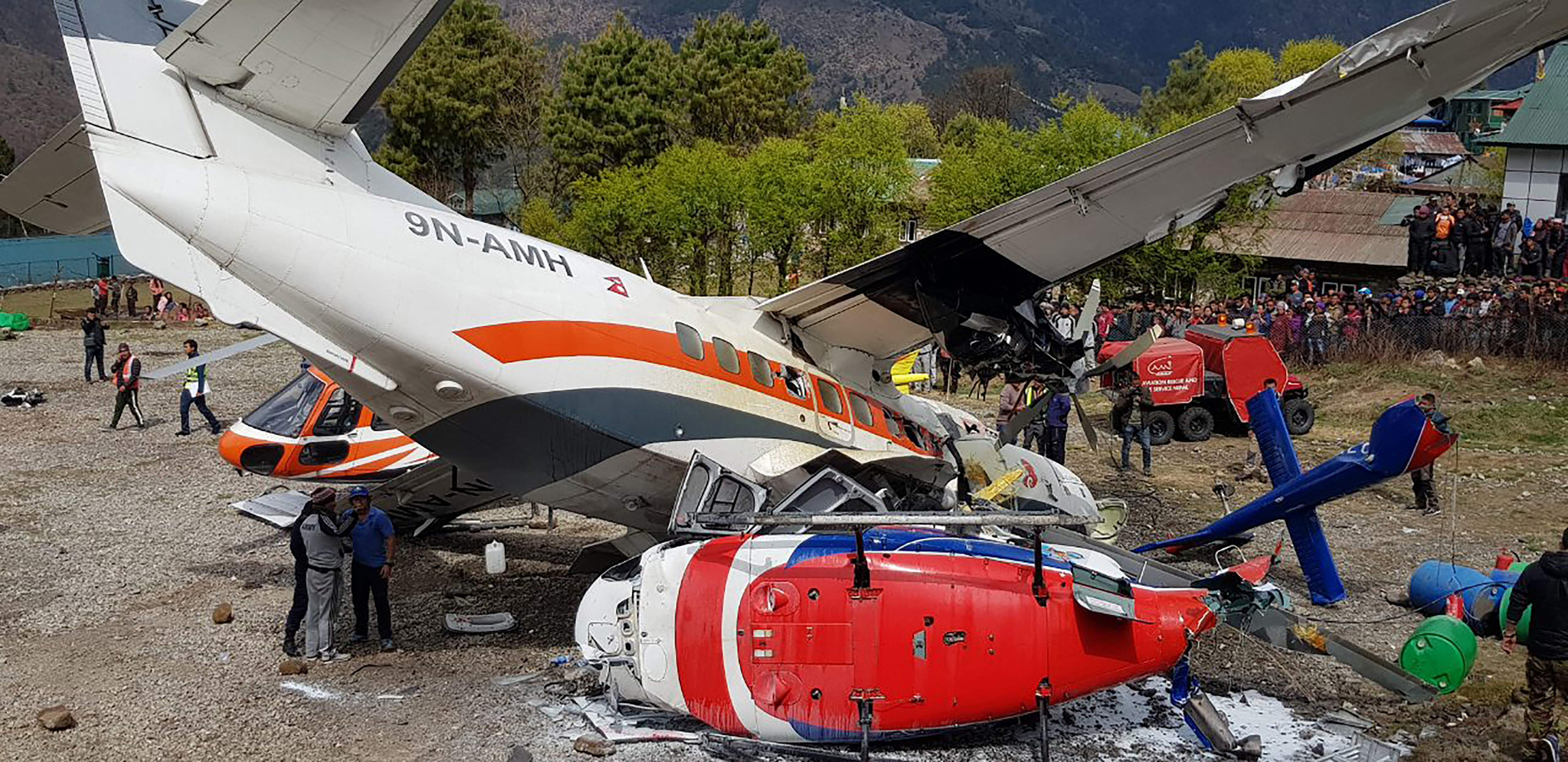 14일(현지시간) 네팔 에베레스트산 관문 루클라의 텐징-힐러리 공항에서 서미트항공 소속 소형비행기가 이륙 도중 주기된 헬리콥터와 충돌했다. [AFP=연합뉴스]