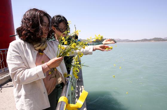 세월호 참사 5주기를 하루 앞둔 15일 전남 진도 팽목항에서 추모객들이 세월호 희생자들의 넋을 기리며 유채꽃을 바다에 뿌리고 있다. [프리랜서 장정필]