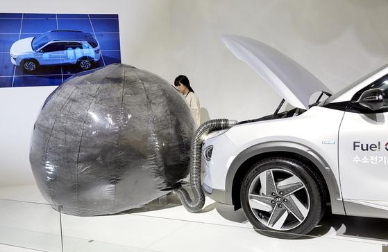 미세먼지 정화 실험을 시작하면 자동차 시동을 켜고 앞쪽의 풍선 안에 검은 탄소가루를 주입한다.