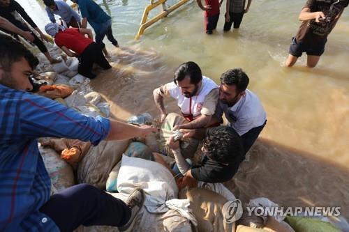 이란 남부 아흐바즈에서 주민들이 수해 복구작업을 벌이고 있다. [AFP=연합뉴스]